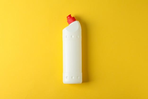 Bottiglia bianca con detergente su giallo