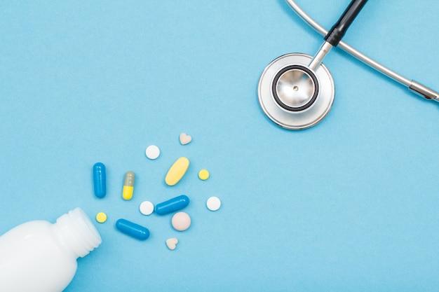 Bottiglia bianca con diverse pillole, capsule e fonendoscopio su sfondo blu. medicinali e attrezzature mediche