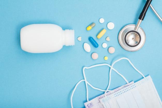 Bottiglia bianca con diverse pillole, fonendoscopio e maschere per il viso su sfondo blu