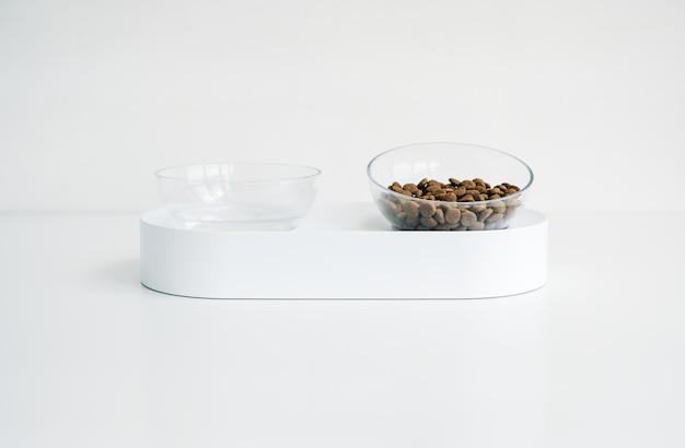 Ciotola bianca per cane o gatto con mangime e acqua isolati su sfondo bianco.