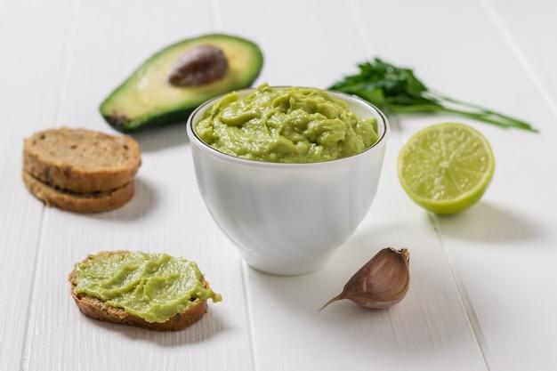Ciotola bianca piena di guacamole fresco e ingredienti per cucinare. dieta vegetariana cibo messicano avocado. cibo crudo.