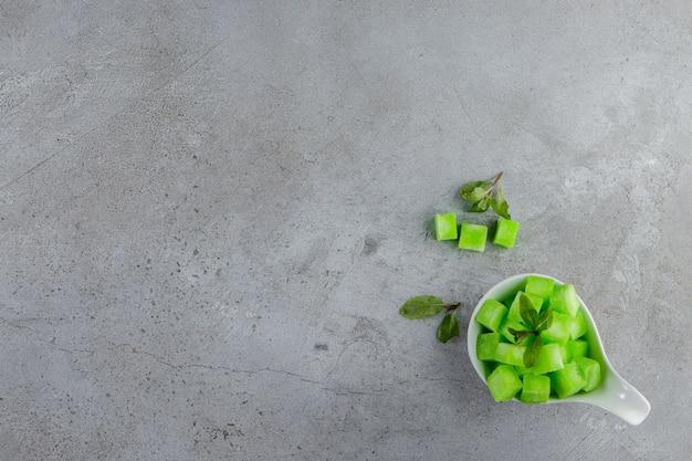 Una ciotola bianca piena di dolci caramelle verdi con foglie di menta su una superficie di pietra