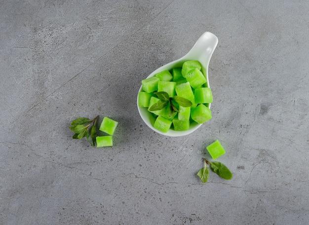 Una ciotola bianca piena di dolci caramelle verdi con foglie di menta su una pietra.