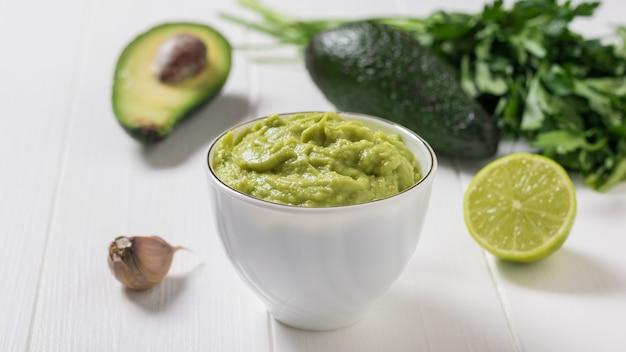 Ciotola bianca con guacamole e avocado su un tavolo di legno bianco. dieta vegetariana cibo messicano avocado. cibo crudo.