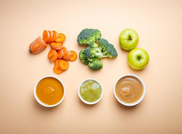 Ciotole bianche con pappe naturali sane su fondo pastello. puree, fatte di frutta e verdura fresca biologica, flay lay, vista dall'alto, concetto. cibo per bambini a base di carote, broccoli, mele
