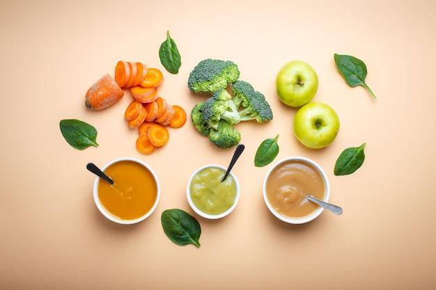 Ciotole bianche con pappe naturali sane su fondo pastello. puree, fatte di frutta e verdura fresca biologica, flay lay, vista dall'alto, concetto. cibo per bambini a base di carote, broccoli, mele, spinaci
