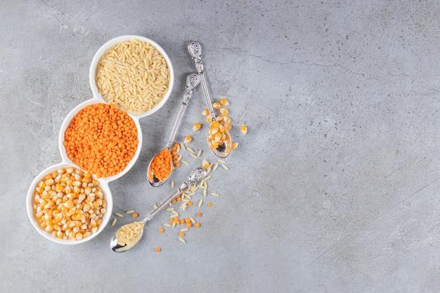 Ciotole bianche con riso crudo, lenticchie e semi su fondo di pietra.