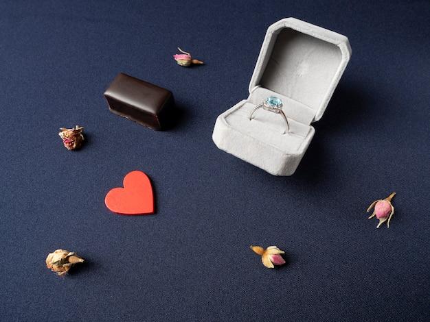 Scatola bianca in cui un anello con una pietra blu, un cuore rosso, cioccolato e boccioli di rose secche giace vicino su un blu