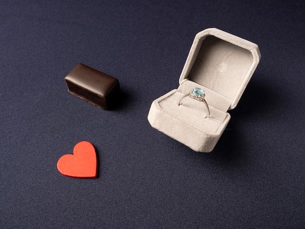 Scatola bianca in cui un anello con una pietra blu, un cuore rosso e cioccolato si trova vicino su un blu