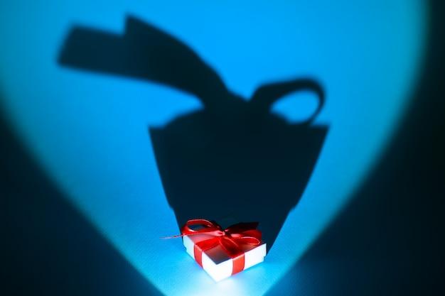 Scatola bianca con un regalo e un arco con una lunga ombra