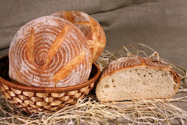 Il pane bianco giaceva in un cesto di paglia su una tovaglia di lino grigia