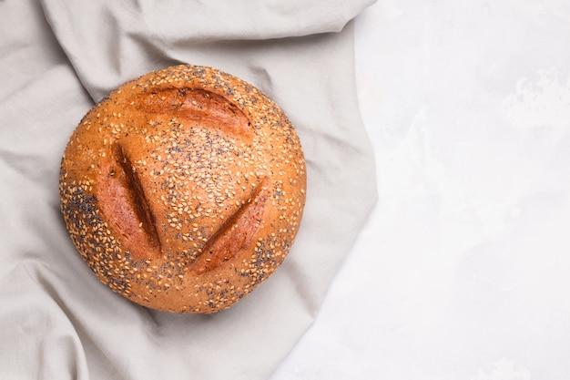 Pane bianco con semi di sesamo e semi di papavero su tela di lino su uno spazio bianco. copia spazio