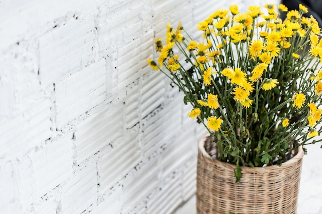 Muro di mattoni bianco con la decorazione interna della natura del canestro del fiore nello stile moden del caffè
