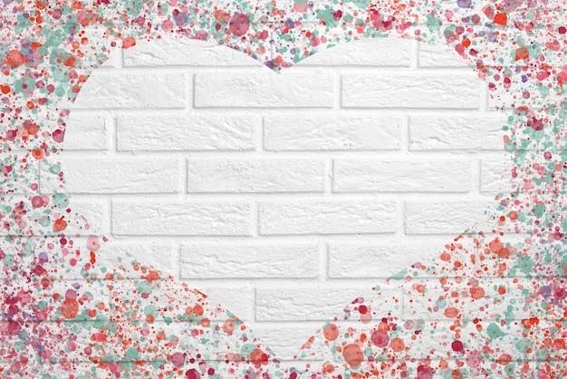 Muro di mattoni bianchi con spruzzi multicolori di vernice e un cuore, un posto per il testo, spazio per le copie