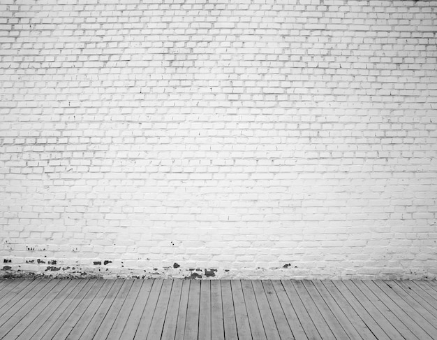 Muro di mattoni bianchi e fondo del pavimento in legno