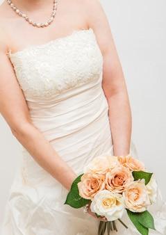 Abito da sposa bianco con bouquet di rose