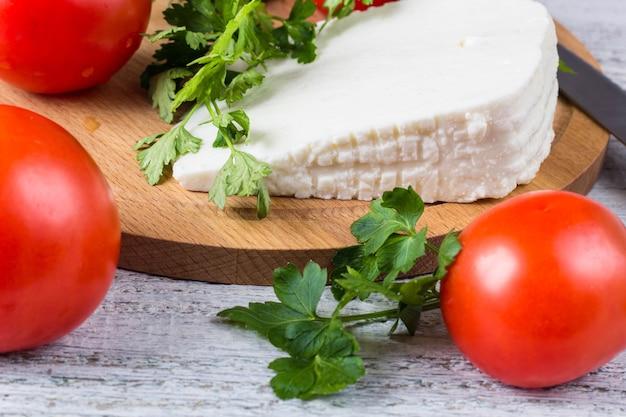 Formaggio di salamoia bianco, coltello, prezzemolo, pomodori su uno sfondo di assi di legno