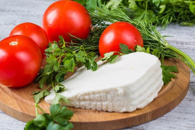 Formaggio in salamoia bianco, coltello, prezzemolo, pomodori su tavole di legno