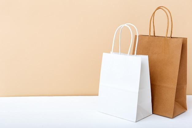 Sacchetti di carta bianca marrone artigianale. il modello di acquisto insacca i pacchetti sul fondo leggero beige della tavola bianca con lo spazio della copia.