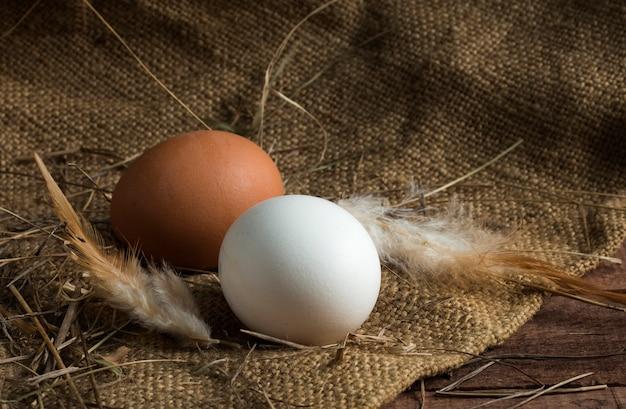 Uova bianche e marroni con piume su un fondo di legno marrone con tela da imballaggio.