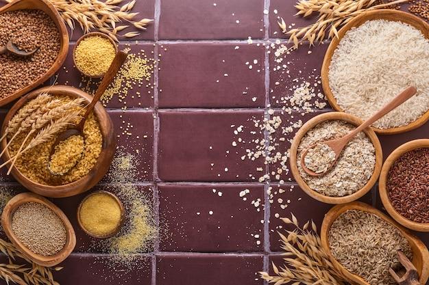 Riso bianco, marrone e rosso, grano saraceno, miglio, semole di mais, quinoa e bulgur in ciotole di legno su un tavolo da cucina in pietra marrone. cereali senza glutine. vista dall'alto con copyspace