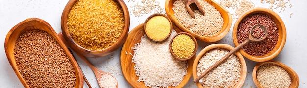 Riso bianco, marrone e rosso, grano saraceno, miglio, semole di mais, quinoa e bulgur in ciotole di legno sul tavolo da cucina grigio chiaro. cereali senza glutine. vista dall'alto con copyspace. bandiera.