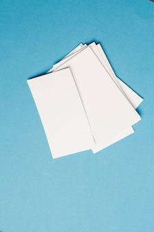 Biglietti da visita bianchi in ufficio su mockup di vista superiore in vetro blu. foto di alta qualità