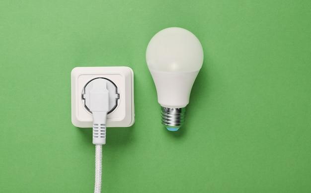 Cavo bianco collegato alla presa di corrente e lampadina a led su sfondo verde. vista dall'alto