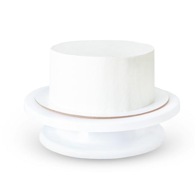 Torta bianca senza decorazioni su un supporto isolato su superficie bianca. anche mockup e campione di torta rotonda.