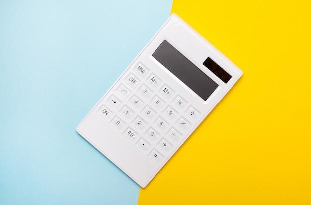 La calcolatrice bianca si trova su sfondi azzurro e giallo. disposizione piatta.