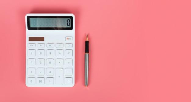 Calcolatore e penna bianchi su un fondo rosa luminoso, sui concetti di vendita e finanziari
