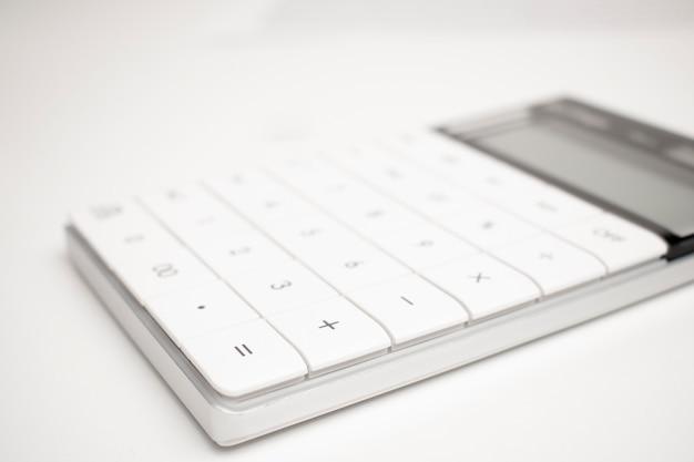 Una calcolatrice bianca su sfondo bianco.