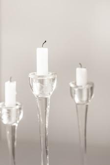 Candele bianche in candelieri di vetro su un design d'interni o un decoro di sfondo bianco