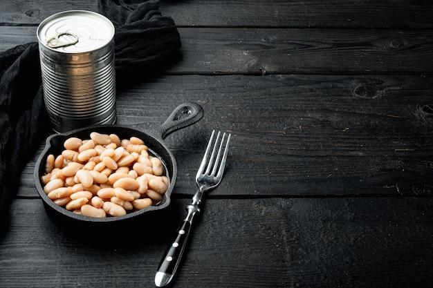 Set di fagioli bianchi in scatola, con lattina in metallo, in padella in ghisa, sul tavolo in legno nero