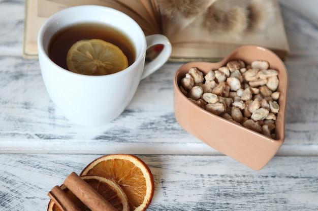 Tappo bianco di tè con mix di limone frutta secca e cioccolato su sfondo bianco