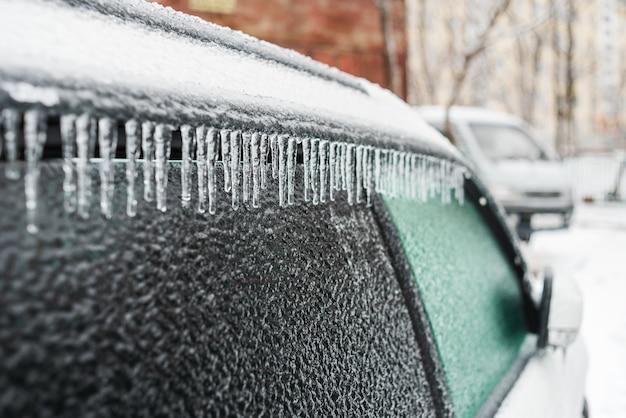Auto bianca ricoperta di ghiaccio e ghiaccioli dopo la pioggia gelata ciclone tempesta di ghiaccio brutto tempo gelido scene di neve invernale