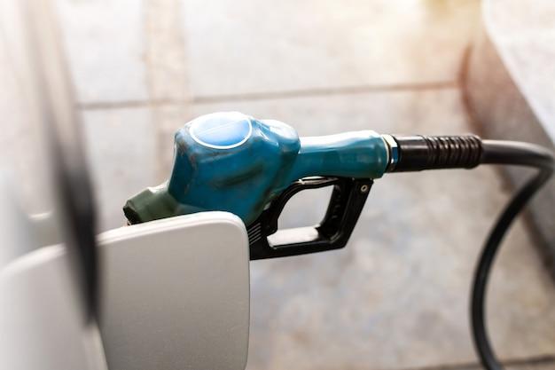 Auto bianca di rifornimento alla stazione di servizio con ugello di carburante blu.