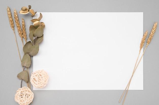 Cartoncino bianco con decorazione di eucalipto essiccato e orecchie dorate su tavola neutra