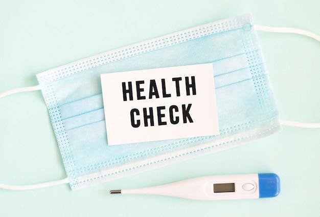Cartellino bianco con la scritta health check su una mascherina protettiva medica.
