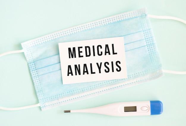 Cartellino bianco con la scritta analisi medica su mascherina protettiva medica