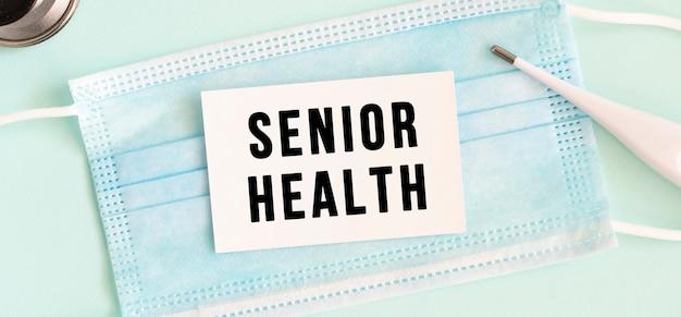 Cartellino bianco con la scritta senior health su una mascherina protettiva medica. concetto medico.