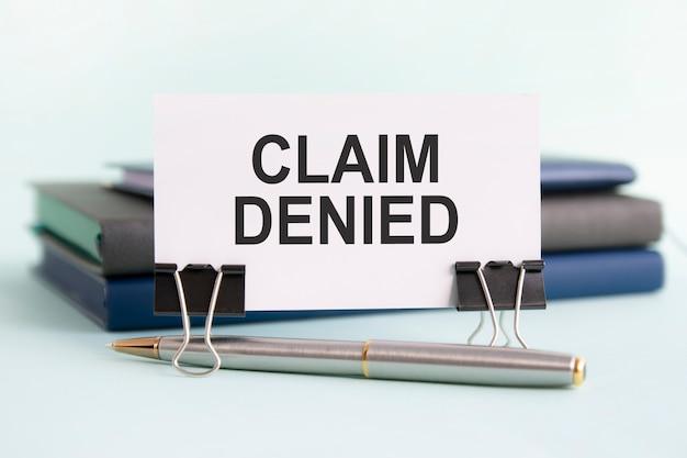 Una carta bianca con la richiesta di testo negata si trova su una clip per documenti sul tavolo sullo sfondo di libri. messa a fuoco selettiva