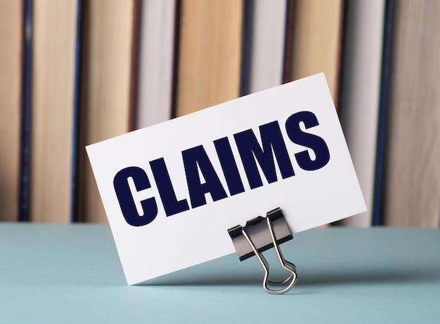 Una carta bianca con il testo reclami si trova su una clip per documenti sul tavolo sullo sfondo dei libri. sfocatura