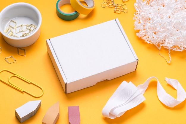 Scatola di cartone bianca sulla scrivania dell'ufficio di colore