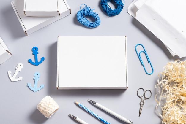 Scatola di cartone bianca sulla scrivania in ufficio, concetto della marina