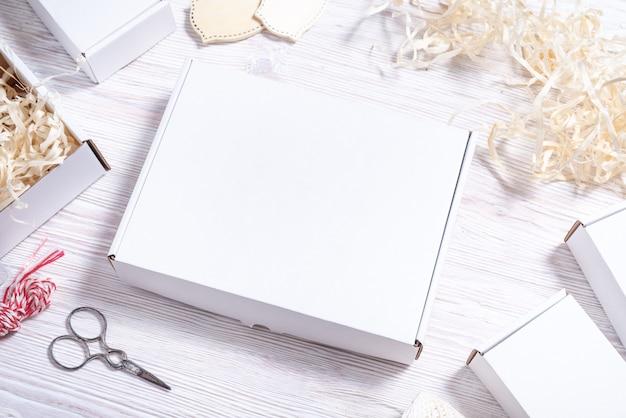 Scatola di cartone di cartone bianco sulla scrivania in legno, mock up piatto lay