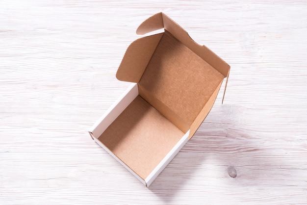Scatola di cartone di cartone bianco sulla scrivania in legno, vista dall'alto