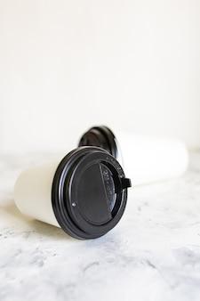 Sul tavolo di marmo giacciono tazze di caffè di cartone bianco