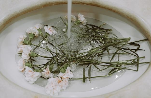 Garofani bianchi in un lavandino con acqua