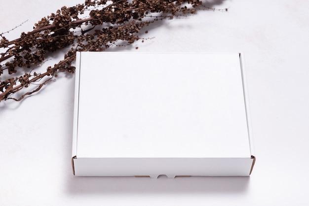 Scatola di cartone bianca decorata con rami secchi, mock up